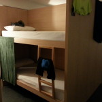 Bunk bed in the hostel. 2 bunk beds by alcove or cubicle.
